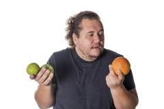 L'uomo grasso divertente tiene i frutti su fondo bianco Perdita di peso e cibo sano fotografia stock