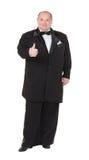 L'uomo grasso elegante in uno smoking mostra il pollice-su Fotografie Stock