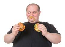 L'uomo grasso esamina Lustfully un hamburger Immagini Stock Libere da Diritti