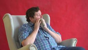 L'uomo grasso isolato sopra un fondo rosso sta starnutendo nel fazzoletto video d archivio