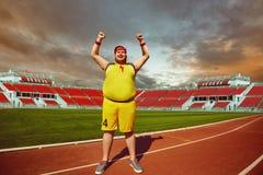 L'uomo grasso nelle grida degli abiti sportivi ha sollevato le mani sullo stare nello stadio fotografie stock libere da diritti