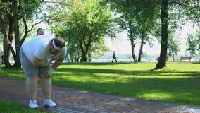 L'uomo grasso ritiene l'attacco di cuore mentre corre, ragazza obesa che lo aiuta, supporto dell'amico stock footage