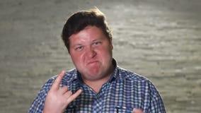L'uomo grasso sta rendendo il segno dei corni nella sera all'aperto archivi video