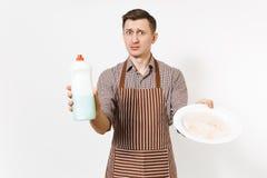 L'uomo in grembiule marrone a strisce, camicia tiene il piatto sporco del giro bianco, detersivo Lavare i piatti con il liquido d immagine stock libera da diritti