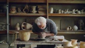 L'uomo grigio-dai capelli laborioso sta lavorando con l'argilla sulla ruota del ` s del vasaio, modellante il pezzo di terriccio  video d archivio