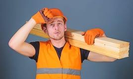 L'uomo in guanti protettivi tiene la visiera del casco protettivo, fondo grigio Carpentiere, falegname, forte costruttore sopra fotografia stock