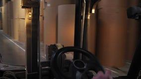 L'uomo guida il caricatore del carrello elevatore lungo il deposito con i rotoli di carta archivi video