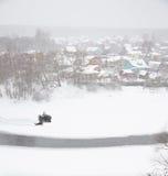 L'uomo guida la bici del quadrato lungo il villaggio del fiume nell'inverno Fotografie Stock