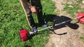 L'uomo guida una treccia della benzina Tira acutamente il cavo iniziante Fissa la falce al sistema della tenda e va falciare video d archivio