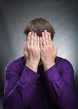 L'uomo ha coperto il suo fronte di mani Fotografie Stock Libere da Diritti
