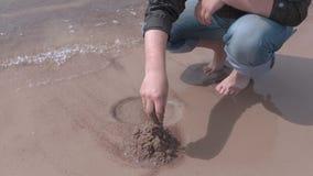 L'uomo ha costruito il castello della sabbia vicino al mare archivi video