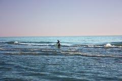 L'uomo ha immerso nella pesca marittima e raccoglie i tellines o vongole o altri frutti di mare un giorno di inverno immagini stock