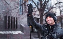 L'uomo ha incontrato un amico nella via nell'inverno ed ha ondeggiato a lui Ascolta musica tramite le cuffie fotografia stock