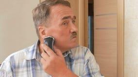 L'uomo ha invecchiato il rasoio elettrico di rasatura nel bagno Guarda nello specchio e con attenzione si rade fuori da tutti i s stock footage