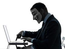 L'uomo ha mascherato la siluetta di calcolo del computer del membro anonimo del gruppo Fotografia Stock