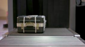 L'uomo ha messo i bagagli al contatore di registrazione all'aeroporto Macchina di raggi x al contatore di registrazione dell'aero video d archivio