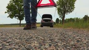 L'uomo ha messo il triangolo d'avvertimento sulla strada vicino all'automobile archivi video