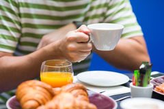 L'uomo ha prima colazione con i croissant, il caffè ed il succo d'arancia fresco immagini stock