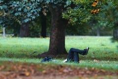 L'uomo ha resto nel parco dell'estate - mettere sull'erba che aumenta le gambe Immagini Stock