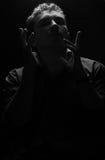 L'uomo ha sollevato le sue mani, sollevate la sua testa e chiuso il suo osserva, pensando a qualcosa Fotografia Stock