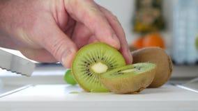 L'uomo ha tagliato con un coltello un dolce fresco e Kiwi Fruit verde succoso in due fette stock footage