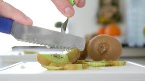 L'uomo ha tagliato con un coltello Kiwi Fruit in molte fette per una macedonia di frutta stock footage
