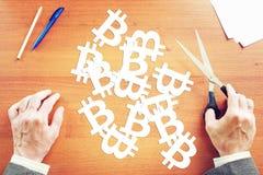 L'uomo ha tagliato da carta molti segni del bitcoin Immagini Stock