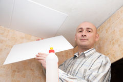 L'uomo incolla le mattonelle del soffitto Fotografia Stock