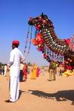 L'uomo indiano che sta con il suo ha decorato il cammello al festival del deserto, Fotografie Stock