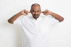 L'uomo indiano di affari casuali maturi ha coperto le orecchie fotografia stock
