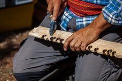 L'uomo indigeno in camicia blu è bordo di dimostrazione di illuminazione del fuoco di tenuta fotografia stock libera da diritti