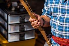 L'uomo indigeno in camicia blu sta giudicando uno strumento primitivo utilizzato per accendere un fuoco di accampamento fotografia stock