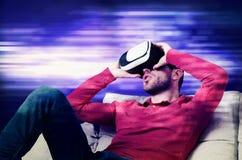 L'uomo indossa i vetri di realtà virtuale con lo smartphone dentro Immagini Stock