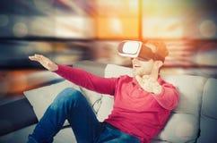 L'uomo indossa i vetri di realtà virtuale con lo smartphone dentro Fotografia Stock