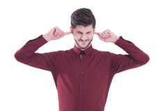 L'uomo infelice e sollecitato che riguarda le suoi orecchie e closing il suo osserva Fotografia Stock Libera da Diritti