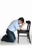 L'uomo inginocchiato prega fotografia stock
