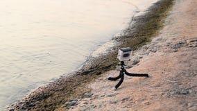 L'uomo installa la macchina fotografica di azione sulla riva video d archivio