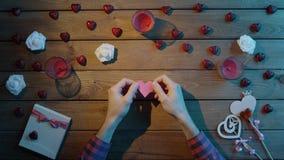 L'uomo interessante con cuore fatto a mano di carta si siede dalla tavola, vista superiore archivi video