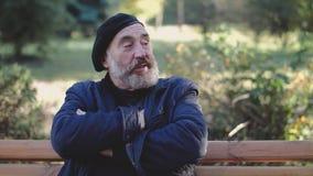 L'uomo invecchiato in cappello riposa con le mani attraversate sul banco di parco e parla ai passanti video d archivio