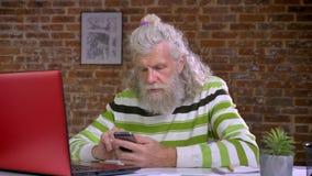 L'uomo invecchiato caucasico fresco sta facendo scorrere il suo telefono cellulare mentre si sedeva nel luogo di lavoro, muro di  stock footage