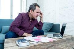 L'uomo invecchiato medio di ribaltamento ha sollecitato circa i debiti della carta di credito e le finanze di stima non felici di fotografia stock