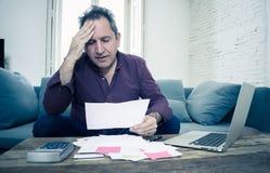 L'uomo invecchiato medio di ribaltamento ha sollecitato circa i debiti della carta di credito e le finanze di stima non felici di fotografia stock libera da diritti