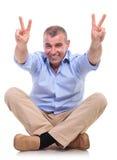 L'uomo invecchiato mezzo casuale si siede e mostra la vittoria Fotografie Stock