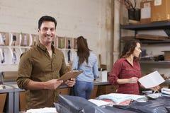 L'uomo ispano imballa gli ordini per distribuzione, sorride alla macchina fotografica immagini stock libere da diritti