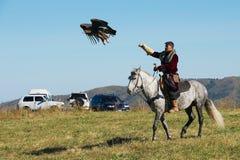 L'uomo kazako sul cavallo cerca con l'aquila reale circa Almaty, il Kazakistan Fotografie Stock Libere da Diritti
