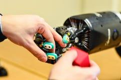 L'uomo lascia la mano meccanica del robot che tiene un cubo rosso nel laboratorio di ricerca fotografie stock libere da diritti