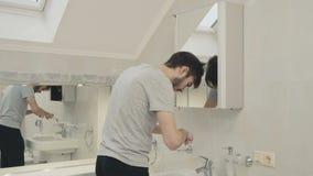 L'uomo lava i denti con lo spazzolino da denti ed il dentifricio in pasta stock footage