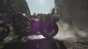 L'uomo lava un motociclo con un pulitore ad alta pressione archivi video