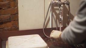 L'uomo lava un pezzo di vetro nel lavandino video d archivio