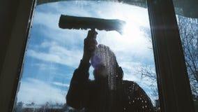 L'uomo lava una finestra sporca sul balcone, uno scalatore industriale schiuma la finestra fuori video d archivio